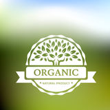Organic product badge with tree on blurred landscape. Vector ill Stock Photo