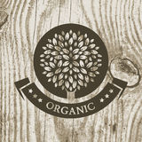 Organic product badge with tree on wooden texture. Vector illust Royalty Free Stock Photo
