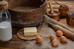Organic products: eggs, milk, bread, butter, wheat on a wooden background stock image