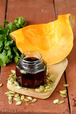 Organic pumpkin oil in a glass jar Royalty Free Stock Image