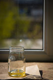Organic pure honey in jar on window sill. Stream of honey Royalty Free Stock Photo