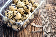 Organic quail eggs. In the container on wooden background. Natural gourmet meal royalty free stock image