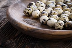 Organic quail eggs. On the wooden plate. Natural gourmet meal stock photos
