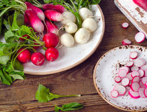 Organic radishes on a rustic wooden table. Stock Photo
