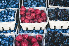 Organic Raspberries, blackberries and blueberries. Raspberries, blackberries and blueberries background in small baskets for sale at a farmers market Stock Photos