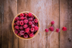 Organic raspberries in a bowl on wooden background. Bright fresh organic raspberries in a bowl on old wooden background Royalty Free Stock Photography
