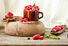 Organic raspberry with basil in a cup of coffee and a wooden sta Royalty Free Stock Images