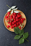 Organic raspberry on wood plate Stock Photography