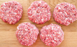 Organic raw ground beef, round patties for making homemade burger on wooden cutting board. Closeup of Organic raw ground beef, round patties for making homemade Royalty Free Stock Photos