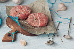Organic raw ground beef wrapped in strips of bacon. Round patties for making homemade burger on wooden cutting board with herbs Royalty Free Stock Images
