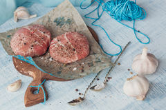Organic raw ground beef wrapped in strips of bacon. Round patties for making homemade burger on wooden cutting board with herbs Stock Images