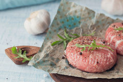 Organic raw ground beef wrapped in strips of bacon. Round patties for making homemade burger on wooden cutting board with herbs Stock Photography