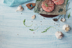 Organic raw ground beef wrapped in strips of bacon. Round patties for making homemade burger on wooden cutting board with herbs. Top view with space for text Stock Photos