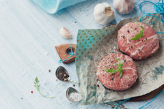 Organic raw ground beef wrapped in strips of bacon. Round patties for making homemade burger on wooden cutting board with herbs. Top view with space for text Royalty Free Stock Image
