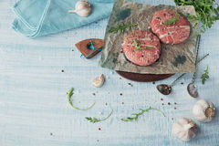 Organic raw ground beef wrapped in strips of bacon. Round patties for making homemade burger on wooden cutting board with herbs. Top view with space for text Stock Image