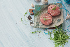 Organic raw ground beef wrapped in strips of bacon. Round patties for making homemade burger on wooden cutting board with herbs. Top view with space for text Royalty Free Stock Photography