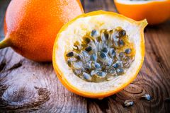 Organic raw ripe yellow granadilla passion fruit. On wooden background stock photos