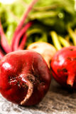 Organic red beets with green leaves on an old wooden table. Rust Stock Image