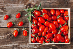 Organic red cherry tomatoes on a wooden board. Organic red cherry tomatoes in a wooden crate on a wooden board/table Stock Photos