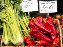 Organic Red Peppers and Celery For Sale. Organic Sweet Ramiro Red Peppers and Celery for sale in the UK, displayed next to each other in a basket Stock Photo