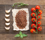 Organic red rice, tomatoes, garlic and herbs on wooden backgroun Royalty Free Stock Photos