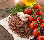 Organic red rice, tomatoes, olive oil, garlic and herbs Royalty Free Stock Photography