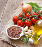 Organic red rice, tomatoes, olive oil, garlic and herbs Stock Photography