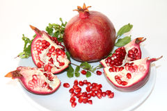 Organic Red Ripe Pomegranate. Organic ripe red pomegranate cut and ready to eat on white plate isolated on white background royalty free stock photography