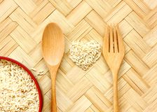 organic rice on bamboo floor .raw rice in heart patter . royalty free stock photos