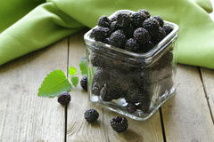 Organic ripe black berry raspberry (blackberry). On a wooden table Royalty Free Stock Photo