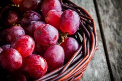 Organic ripe grapes in the basket on wooden table Stock Photo