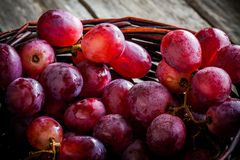 Organic ripe grapes шт the basket on wooden table Stock Images