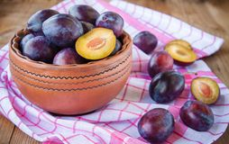 Organic ripe plums in a clay bowl Stock Image