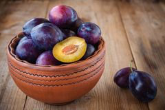 Organic ripe plums in a clay bowl Royalty Free Stock Photography