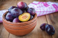 Organic ripe plums in a clay bowl Royalty Free Stock Photos