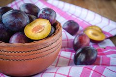 Organic ripe plums in a clay bowl Stock Photo