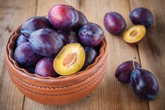 Organic ripe plums in a clay bowl Royalty Free Stock Image
