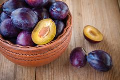 Organic ripe plums in a clay bowl Royalty Free Stock Images
