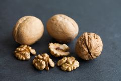 Organic ripe walnut harvest on black stone background. Macro view Stock Image