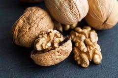 Organic ripe walnut harvest on black stone background. Macro view Royalty Free Stock Image
