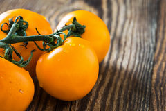 Organic ripe yellow cherry tomatoes on wooden background Royalty Free Stock Photos