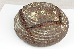 Organic Rye Bread Loaf. Whole, organic, round, dark rye bread loaf with rings and cracks on white and tan Stock Photo