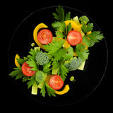 Organic salad on a black plate Royalty Free Stock Photos