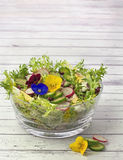 Organic salad decorated with edible pansy flowers on wooden back Royalty Free Stock Photos