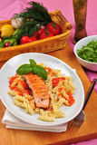 Organic salmon on some tomato pasta. Grilled organic salmon on some tomato pasta Stock Photo