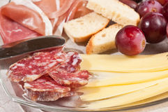 Organic and savory treats for a wine tasting event. Organic treats of sliced salami, prosciutto, crusty bread and red grapes on a clear glass plate with an Stock Photography