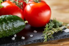 Organic closeup still life of assorted fresh vegetables and herbs on rustic wooden background, topview, selective focus. Organic seasoning close-up still life Stock Images