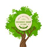 Organic shop emblem over green tree Stock Image