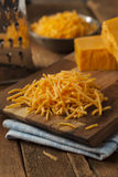 Organic Shredded Sharp Cheddar Cheese. On a Cutting Board royalty free stock photos