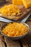 Organic Shredded Sharp Cheddar Cheese. On a Cutting Board royalty free stock images